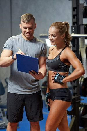 trainers: fitness, sport, exercising and diet concept - smiling young woman and personal trainer with clipboard writing exercise plan in gym