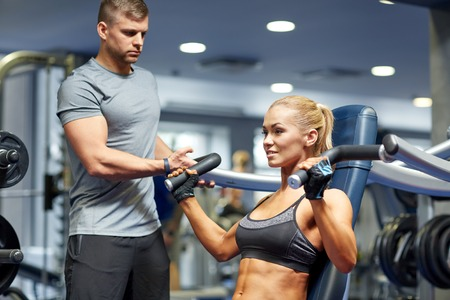 personal safety: sport, fitness, bodybuilding, teamwork and people concept - young woman and personal trainer flexing muscles on gym machine Stock Photo