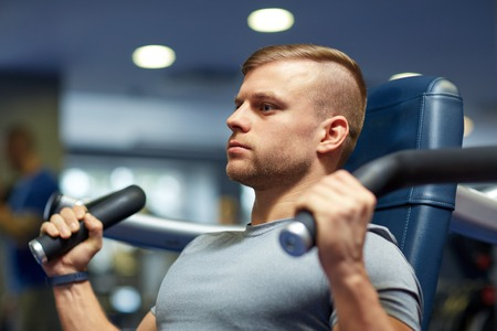 sport, fitness, bodybuilding, lifestyle and people concept - man exercising and flexing muscles on gym machine 版權商用圖片