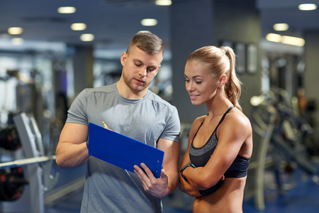 personal training: fitness, sport, exercising and diet concept - smiling young woman and personal trainer with clipboard writing exercise plan in gym