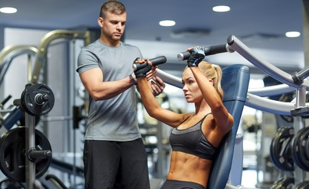 sport, fitness, bodybuilding, teamwork and people concept - young woman and personal trainer flexing muscles on gym machine 스톡 콘텐츠