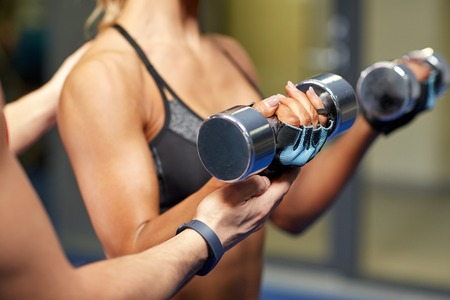 a close up: fitness, sport, bodybuilding and weightlifting concept - close up of young woman and personal trainer with dumbbells flexing muscles in gym Stock Photo