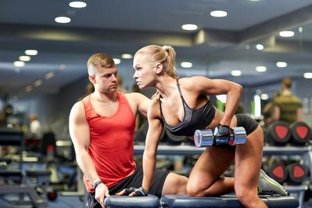 フィットネス、スポーツ、運動、ボディビル、ウエイトリフティング コンセプト - 若い女性やジムでの筋肉がうごめくダンベルを持つパーソナル ト