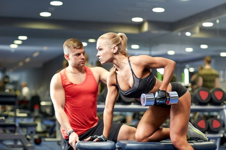 fitness, sport, exercising, bodybuilding and weightlifting concept - young woman and personal trainer with dumbbells flexing muscles in gym