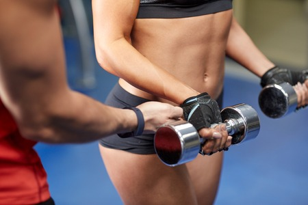 personal training: fitness, sport, bodybuilding and weightlifting concept - close up of young woman and personal trainer with dumbbells flexing muscles in gym Stock Photo