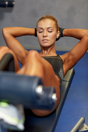 situp: fitness, sport, training and lifestyle concept - woman flexing abdominal muscles on bench in gym