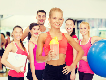 coach sport: sport, fitness and diet concept - smiling sporty woman with protein shake bottle
