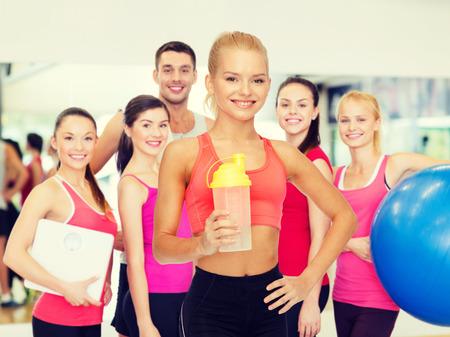 sport, fitness en voeding concept - lachende sportieve vrouw met proteïne shake fles Stockfoto