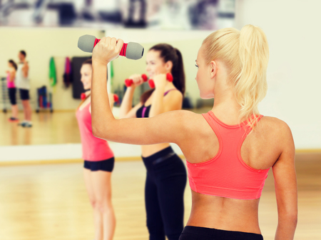 pumping: fitness, sport and diet concept - young sporty woman with light dumbbell