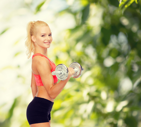 fitness, healthcare and exercise concept - young sporty woman with heavy steel dumbbell