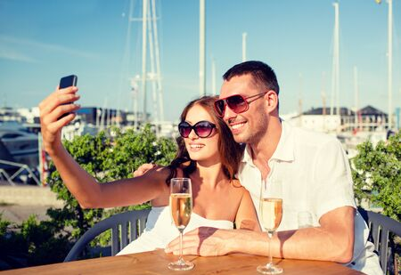 dating: love, dating, people and holidays concept - smiling couple wearing sunglasses drinking champagne and making selfie at cafe