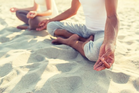 fitness, sport, people and lifestyle concept - close up of couple making yoga exercises sitting on pier outdoors. Stock Photo