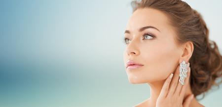 mensen, schoonheid, sieraden en accessoires concept - mooie vrouw met diamanten oorbellen over blauwe achtergrond