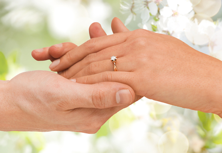 engagements: jewelry, couple, love and wedding concept - close up of man and woman hands with engagement ring over summer garden and cherry blossom background