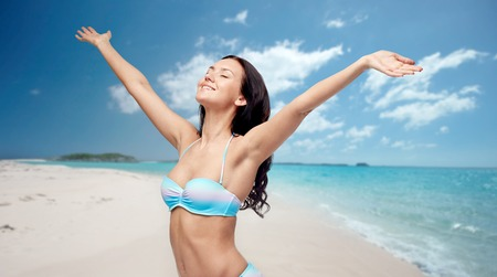 model nice: people, tourism, travel and summer concept - happy young woman in bikini swimsuit with raised hands over beach background