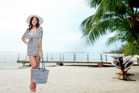 people, fashion, tourism, travel and summer concept - happy young woman in summer clothes and sun hat with bag over berth on tropical beach background