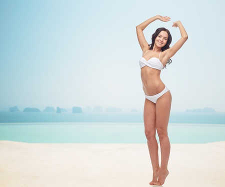 beach girl: people, fashion, swimwear, summer and beach concept - happy young woman posing in white bikini swimsuit with raised hands over infinity pool at beach resort