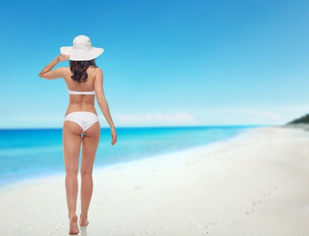 people, swimwear, beauty, travel and summer concept - young woman in white bikini swimsuit from back over beach background Stock Photo