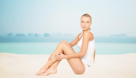 beleza: pessoas, beleza, spa e resort conceito - mulher bonita na cueca de algodão sobre o infinito piscina de borda fundo