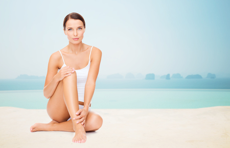 legs  white: people, beauty, spa and resort concept - beautiful woman in cotton underwear touching her legs over infinity edge pool background