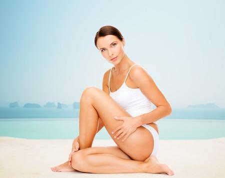 piernas sexys: personas, belleza, spa y resort concepto - mujer hermosa en ropa interior de algod�n de tocar sus caderas sobre piscina de borde infinito fondo