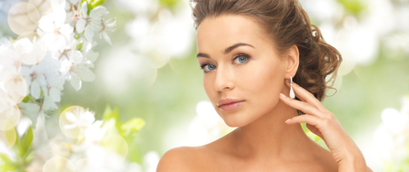 jewelleries: people, beauty, jewelry and accessories concept - beautiful woman with diamond earrings over summer garden and cherry blossom background