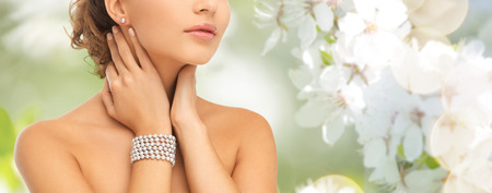 string of pearls: beauty, people and jewelry concept - close up of beautiful woman with pearl earrings and bracelet over summer garden and cherry blossom background
