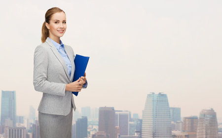 Accountant: business, people and education concept - smiling young businesswoman with holding over city background
