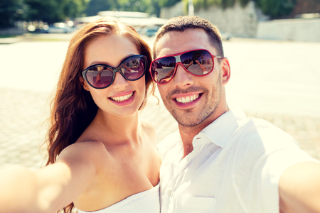 street love: love, wedding, summer, dating and people concept - smiling couple wearing sunglasses making selfie in city