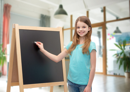 people, children, advertisement and education concept - happy little girl with blackboard and chalk over school class room background