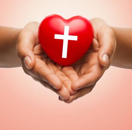 cristianismo: religión, cristianismo y el concepto de la caridad - cerca de las manos femeninas celebración de corazón rojo con el símbolo de la cruz cristiana sobre fondo beige Foto de archivo
