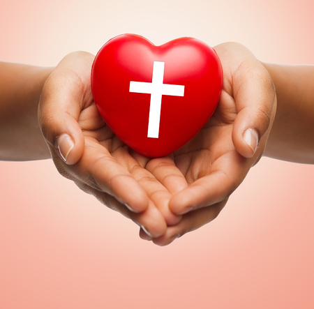 the religion: religion, christianity and charity concept - close up of female hands holding red heart with christian cross symbol over beige background