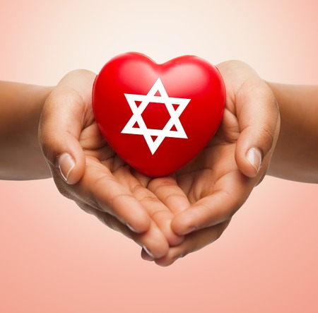 jewish star: religion, christianity, jewish community and charity concept - close up of female hands holding red heart with star of david symbol over beige background