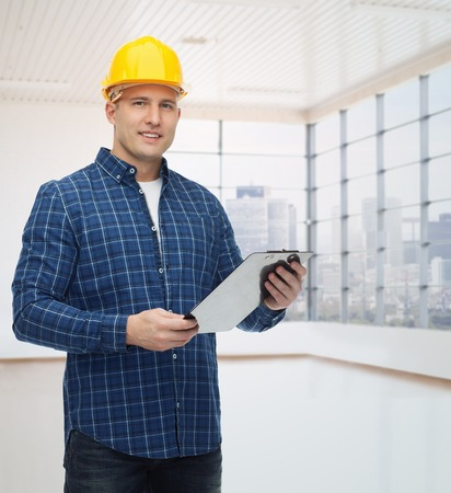 empty of people: repair, construction, building, people and maintenance concept - smiling male builder or manual worker in helmet with clipboard over empty flat background
