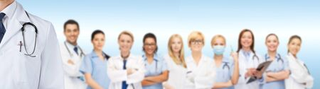 doctors smiling: medicine, profession, teamwork and healthcare concept - international group of smiling medics or doctors over blue background Stock Photo