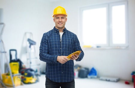 helmet construction: repair, building, construction and maintenance concept - smiling man in helmet with gloves over storeroom background