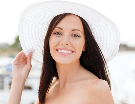 girl in a hat: summer holidays and vacation concept - girl in hat standing on the beach Stock Photo