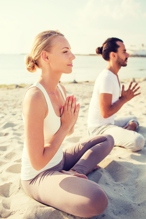team lotus: fitness, sport, friendship and lifestyle concept - smiling couple making yoga exercises sitting on sand outdoors