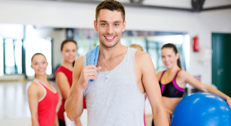personas de pie: fitness, deporte, entrenamiento, gimnasio y estilo de vida concepto - sonriente hombre de pie delante del grupo de personas en el gimnasio Foto de archivo