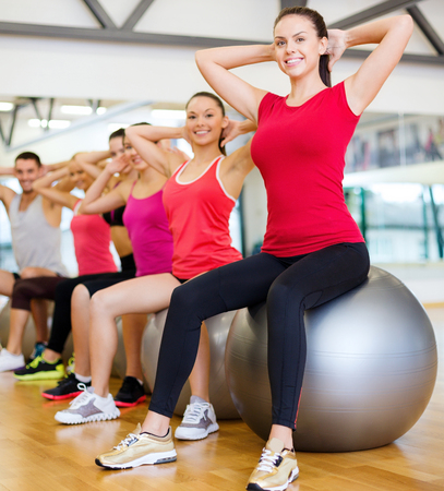 pilates man: fitness, sport, training, gym and lifestyle concept - group of smiling people working out in pilates class Stock Photo