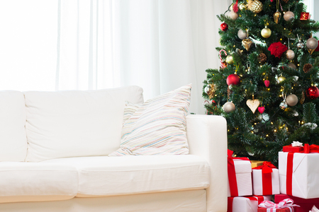 tree of life: winter holidays, decoration and celebration concept - christmas tree, gift boxes and sofa at home room