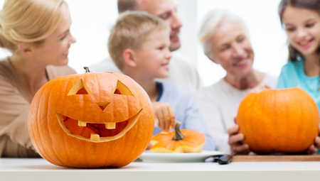 happy holidays: generation, holidays and people concept - helloween pumpkin lantern over happy family at home