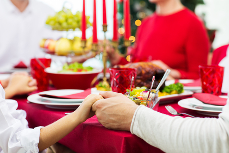 dinner dish: family, holiday, tradition, generation and people concept - close up of family having christmas dinner and holding hands at home Stock Photo