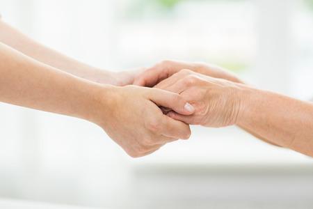 cogidos de la mano: las personas, la edad, la familia, la atención y el apoyo concepto - cerca de la mujer mayor y una mujer sosteniendo jóvenes manos