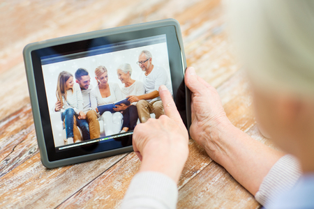 pointing at: technology, age, memories and people concept - happy senior woman with tablet pc computer viewing family photo album at home Stock Photo