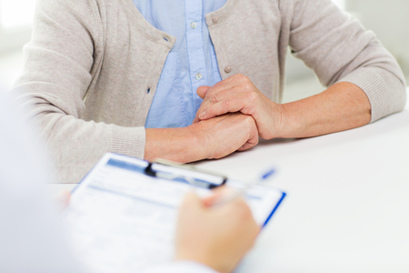 prescribing: medicine, age, health care and people concept - close up of senior woman and doctor hands with clipboard meeting in medical office Stock Photo