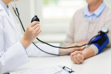 geneeskunde, leeftijd, gezondheidszorg en mensen concept - close-up van arts met tonometer controleren van senior vrouw bloed drukniveau in het ziekenhuis