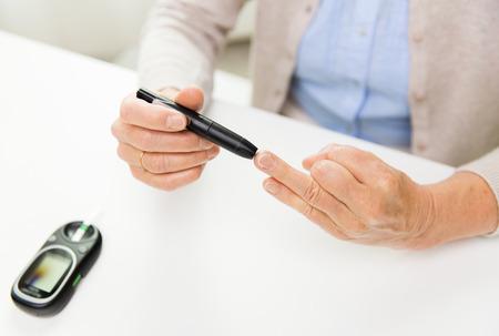 azucar: la medicina, la edad, la diabetes, la salud y las personas concepto - cerca de la mujer mayor con el gluc�metro revisar el nivel de az�car en la sangre en casa Foto de archivo