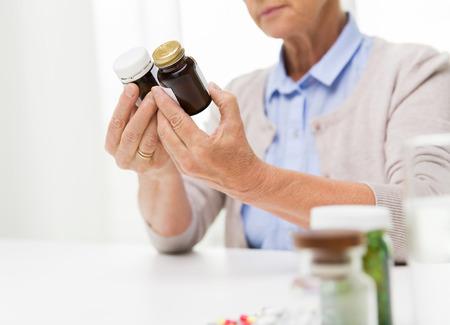 sano: la edad, la medicina, la salud y las personas concepto - cerca de la mujer mayor que mira frascos con la medicina en el hogar o la oficina del hospital Foto de archivo