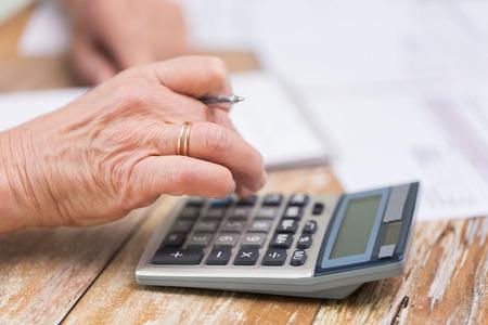 calculadora: negocio, ahorros, seguros de rentas, la edad y el concepto de la gente - la mujer mayor con la calculadora y documentos de contar en el hogar Foto de archivo